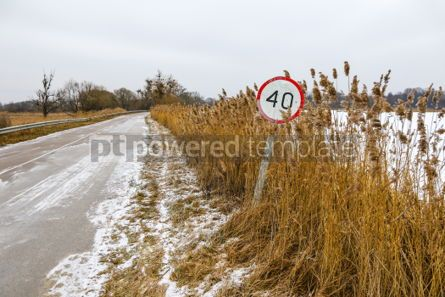 Nature: Winter road with old speed limit sign #03316