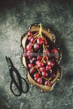 Food & Drink: Red grapes in cupronickel platter on a gray background. #05223