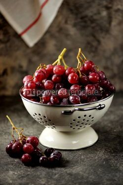 Food & Drink: Red grapes in a white colander on a gray background. #05225