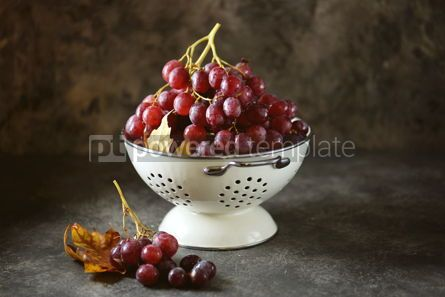 Food & Drink: Red grapes in a white colander on a gray background. #05227