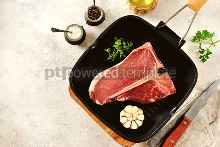 Food & Drink: Fresh raw organic beef t-bone steak on a light background. Top view.  #05296