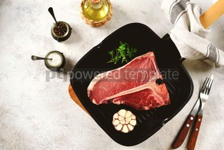 Food & Drink: Fresh raw organic beef t-bone steak on a light background. Top view.  #05297