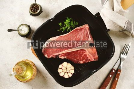 Food & Drink: Fresh raw organic beef t-bone steak on a light background. Top view.  #05298
