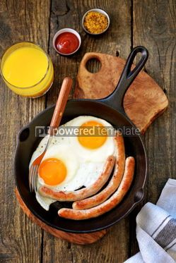 Food & Drink: Fried eggs and thin sausages in a cast iron skillet. Breakfast. Top view.  #05306