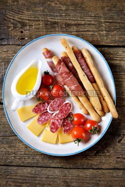 Food & Drink: Antipasti snacks - sausage homemade grissini with jamon cheese cherry tomatoes and olive oil.  #05343