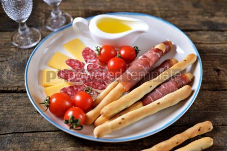 Food & Drink: Antipasti snacks - sausage homemade grissini with jamon cheese cherry tomatoes and olive oil.  #05345
