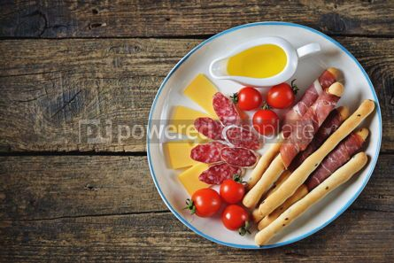 Food & Drink: Antipasti snacks - sausage homemade grissini with jamon cheese cherry tomatoes and olive oil.  #05346