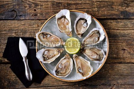 Food & Drink: Fresh oysters with slices of lemon on ice on old wooden background. Top view.  #05348
