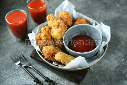 Food & Drink: Delicious homemade deep fried breaded chicken wings with tomato sauce on a gray background.  #07595