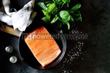 Food & Drink: Fresh raw uncooked salmon in a cast iron pan on a black background. Healthy food.  #07630