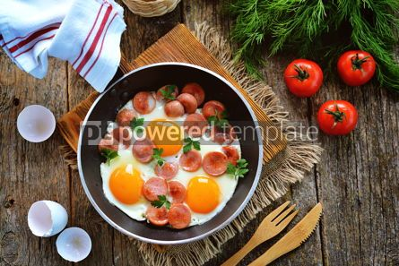 Food & Drink: Homemade fried eggs with sausages in a frying pan on wooden background #13572