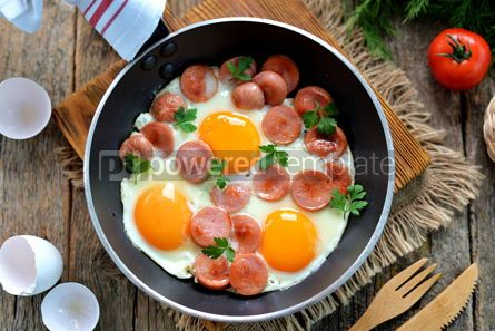 Food & Drink: Homemade fried eggs with sausages in a frying pan on wooden background #13573