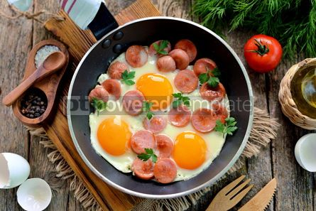 Food & Drink: Homemade fried eggs with sausages in a frying pan on wooden background #13574
