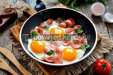 Food & Drink: Homemade fried eggs with sausages in a frying pan on wooden background #13575