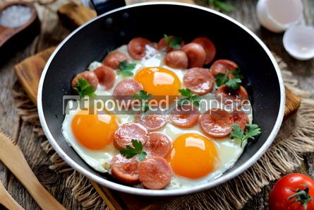 Food & Drink: Homemade fried eggs with sausages in a frying pan on wooden background #13576