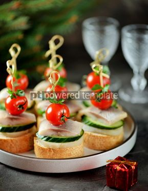 Food & Drink: Canape with salted herring cucumber boiled potatoes and cherry tomato on rye croutons Christmas b #13666