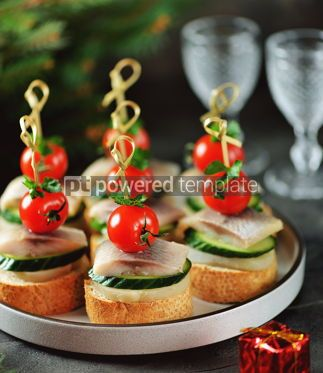 Food & Drink: Canape with salted herring cucumber boiled potatoes and cherry tomato on rye croutons Christmas b #13667