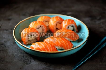 Food & Drink: Philadelphia homemade sushi rolls in a blue plate on a black background #13764