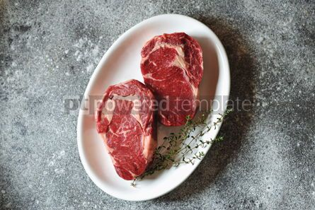 Food & Drink: Juicy raw steak with thyme on a gray background Organic healthy food Top view #13941