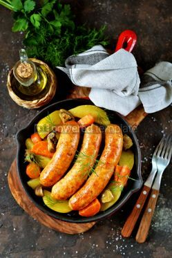 Food & Drink: Roast Chicken sausages with potatoes onions carrots and mushrooms in a cast-iron pan #14097