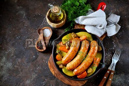 Food & Drink: Roast Chicken sausages with potatoes onions carrots and mushrooms in a cast-iron pan #14098