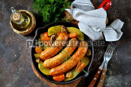 Food & Drink: Roast Chicken sausages with potatoes onions carrots and mushrooms in a cast-iron pan #14100