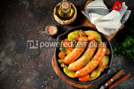 Food & Drink: Roast Chicken sausages with potatoes onions carrots and mushrooms in a cast-iron pan #14104