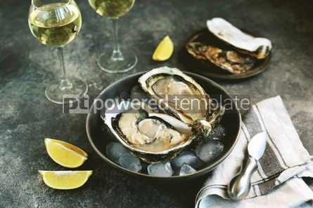 Food & Drink: Giant fresh uncooked oysters in a shell with lemon on ice Healthly food #14255