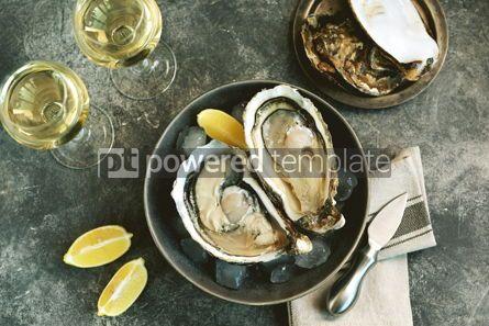 Food & Drink: Giant fresh uncooked oysters in a shell with lemon on ice Healthly food Top view #14258