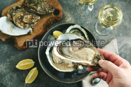 Food & Drink: Giant fresh uncooked oysters in a shell with lemon on ice Healthly food Top view #14259