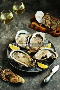 Food & Drink: Giant fresh uncooked oysters in a shell with lemon on ice Healthly food #14263