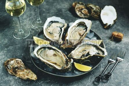 Food & Drink: Giant fresh uncooked oyster in a shell with lemon on ice Healthly food #14282