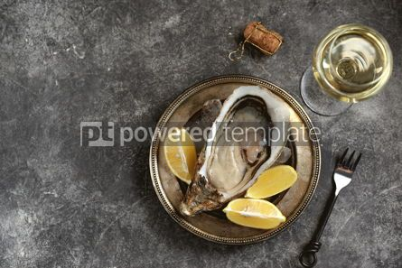 Food & Drink: Giant fresh uncooked oyster in a shell with lemon on ice Healthly food Top view #14283