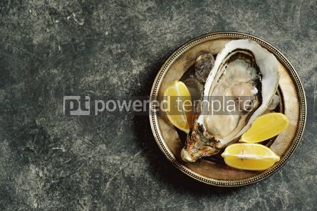 Food & Drink: Giant fresh uncooked oyster in a shell with lemon on ice Healthly food Top view #14284