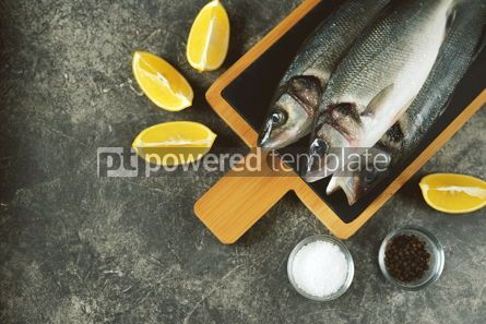 Food & Drink: Three fresh raw sea bass on a serving board on a gray background Top view Copy space #14362
