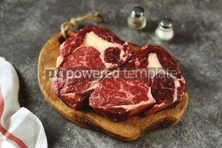 Food & Drink: Two raw fresh beef steak rib eye on olive board on dark background #14377