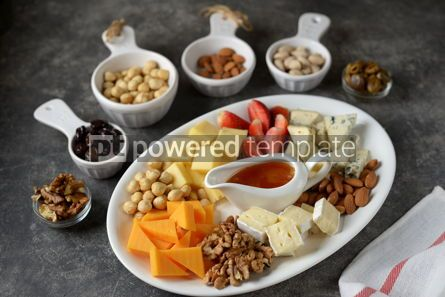 Food & Drink: Various types of cheeses with olives nuts fruits and honey Appetizer for a wine party #14380