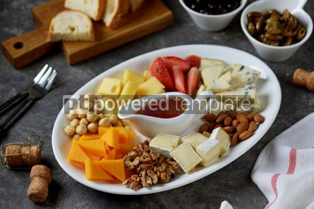 Food & Drink: Various types of cheeses with olives nuts fruits and honey Appetizer for a wine party #14384
