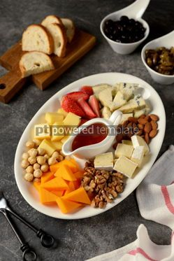 Food & Drink: Various types of cheeses with olives nuts fruits and honey Appetizer for a wine party #14386