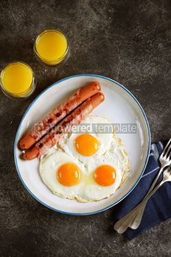Food & Drink: Fried eggs with sausages in bacon and orange juice Traditional hearty breakfast #14484