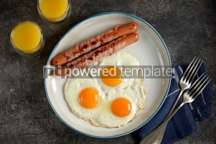 Food & Drink: Fried eggs with sausages in bacon and orange juice Traditional hearty breakfast #14485
