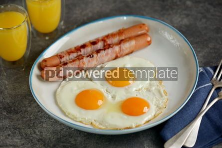 Food & Drink: Fried eggs with sausages in bacon and orange juice Traditional hearty breakfast #14486