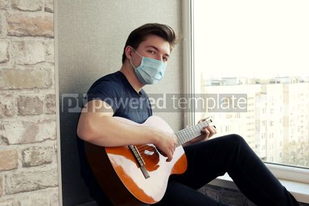 Health: Young guy in a medical mask plays the guitar Home entertainment in isolation #15377