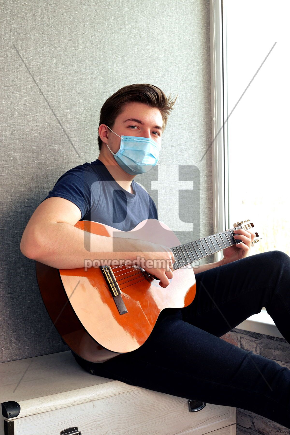 Young guy in a medical mask plays the guitar Home entertainment in isolation, 15378, Health — PoweredTemplate.com