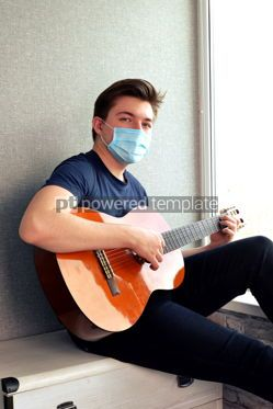 Health: Young guy in a medical mask plays the guitar Home entertainment in isolation #15378