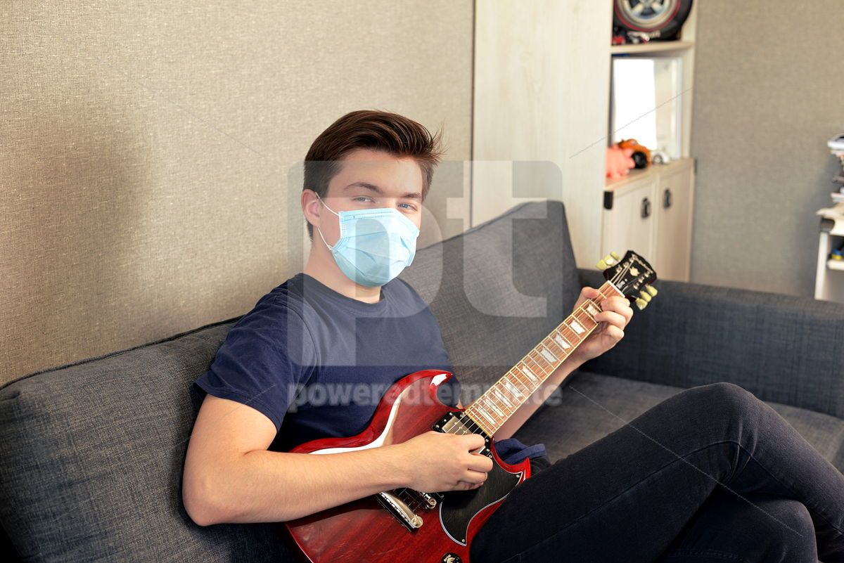Young guy in a medical mask plays the guitar Home entertainment in isolation, 15736, Health — PoweredTemplate.com