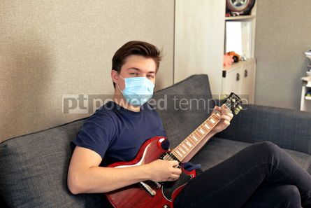 Health: Young guy in a medical mask plays the guitar Home entertainment in isolation #15736