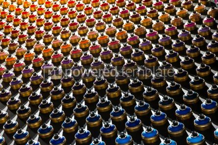 Abstract: Rows of color paint spray cans placed on a black wall #16456